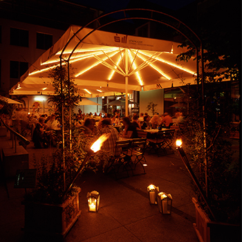 An umbrella with lights illuminating an outdoor bar